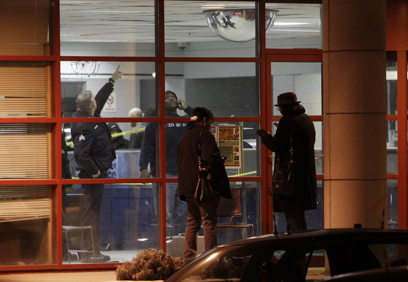 Detroit police officers inspect the scene inside and outside the Precinct 6 building in northwest Detroit, where a gunman walked into the police station and opened fire, wounding three officers on Sunday. The gunman was killed as the police returned fire.