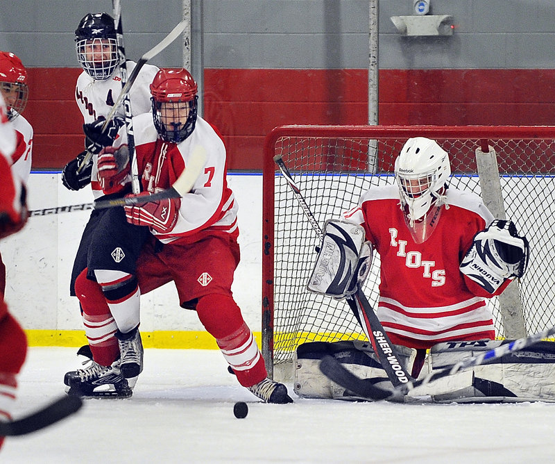 South Portland goalie Dominic Desjardins, and Josh Cobb, 7, keep their eyes on a loose puck in front. Scarborough scored three straight goals for a 3-1 victory.