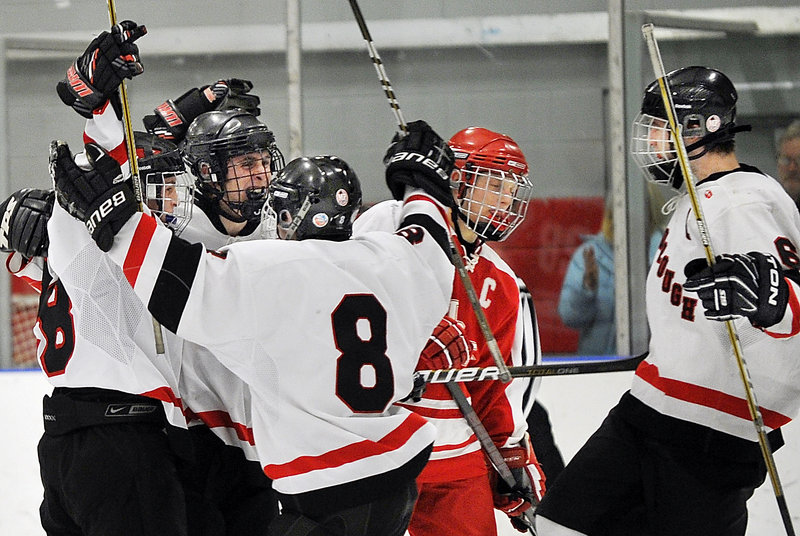 Tommy Ellis of South Portland can only skate by Thursday night as Scarborough celebrates a second-period goal that tied the game. Jacob Gross, left, scored it, with Connor Gullifer, 8, and Kyle Nablo celebrating.