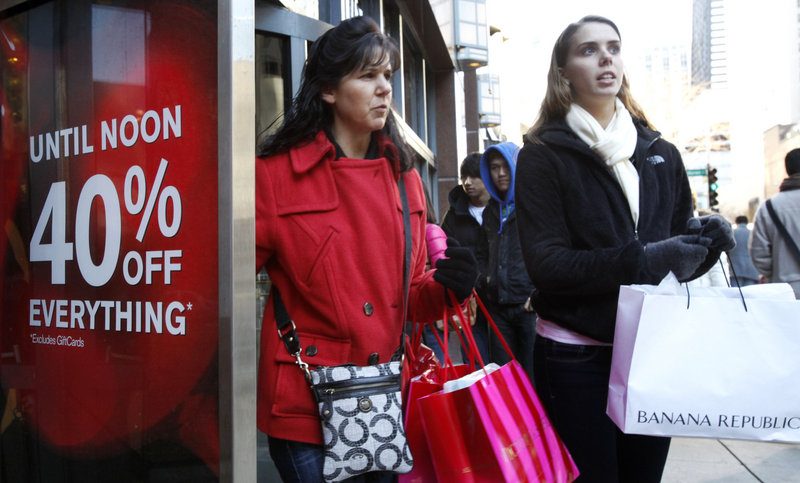 Shoppers walk out of the Express women's apparel store on Chicago's Magnificent Mile in November. The economy gained strength at the end of last year as Americans spent at the fastest pace in four years and U.S. companies sold more overseas.