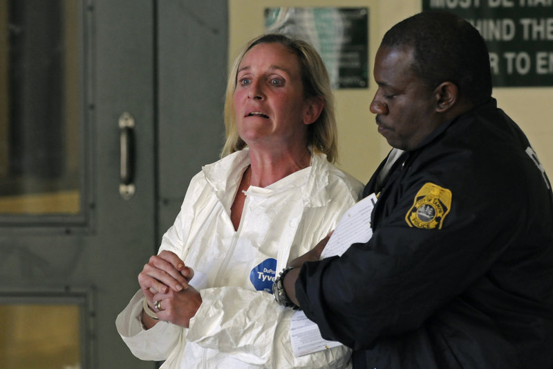 A police officer escorts Julie Powers Schenecker to jail Friday in Tampa, Fla. Schenecker left a note saying