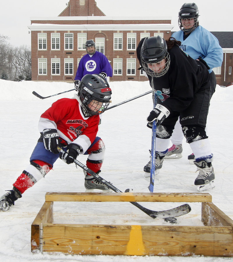 Levi Guay, 7, of Sabattus scores against Melissa Bourgoin of Lewiston during the 3-on-3 Pond Hockey Tournment at the Walton School. The tournament drew eight teams – all adults, except for Levi – and raised funds for the Auburn Youth Hockey League.