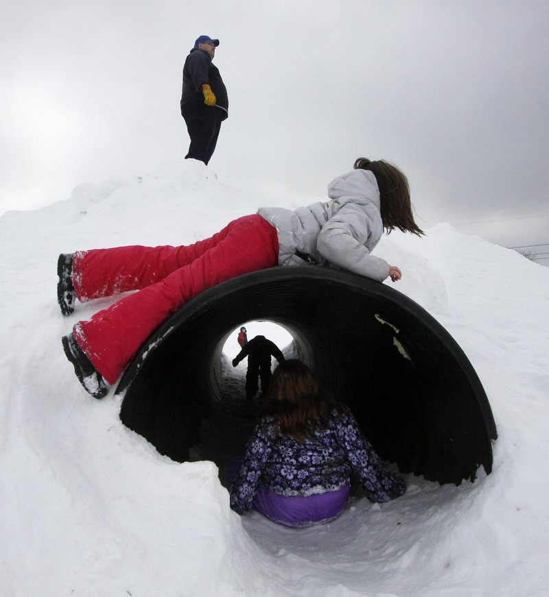 Children make the most of a culvert at the winter playground set up at Walton Field in Auburn.