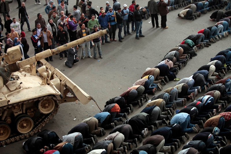 Anti-government protesters bow in prayer in front of an Egyptian army tank during a protest in Tahrir Square in Cairo on Saturday.