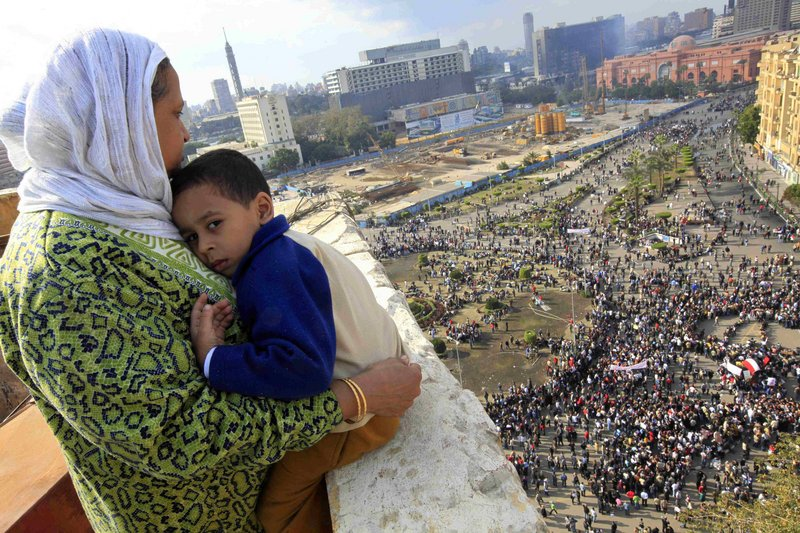 An Egyptian mother hugs her child as she watches some thousands of Egyptian protesters gather at Tahrir Square in Cairo on Sunday.