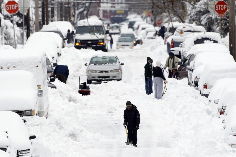 A young pedestrian makes his way down a snow-covered street after a winter storm in Philadelphia last week. Scientists who accept climate change cite several reasons for an increase in snow, including the loss of Arctic sea ice and the effect that change has on the winds circling the North Pole.