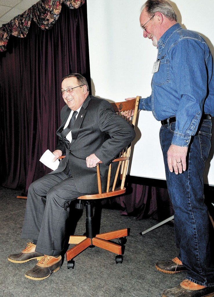 Gov. Paul LePage tries out a handmade wooden chair given by Dan Maxham, president of W.A. Mitchell Fine Furniture company in Farmington, during the annualmeeting of the Maine Wood Products Association on Wednesday. LePage was the keynote speaker.