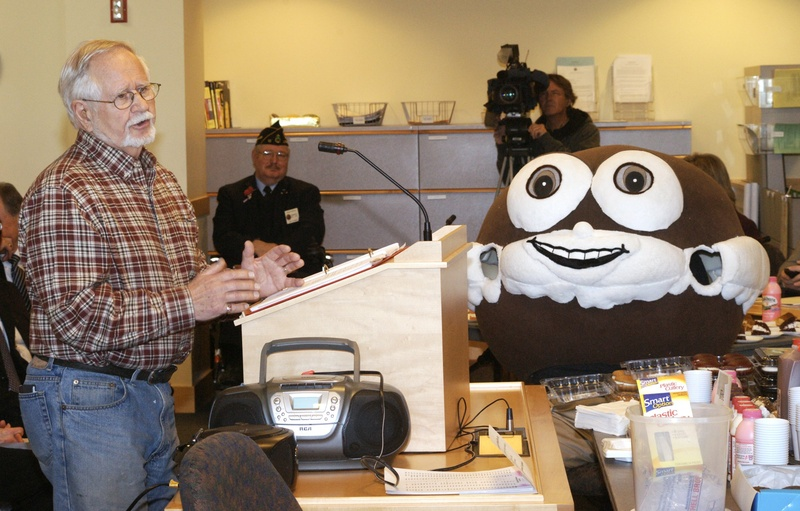 "John Linscott, who wrote lyrics about whoopie pies, testifies last month in Augusta under the watchful eyes of a man dressed as a whoopie pie. On Monday, a legislative panel amended a proposed bill to say that the whoopie pie would be the state's official ""treat."""