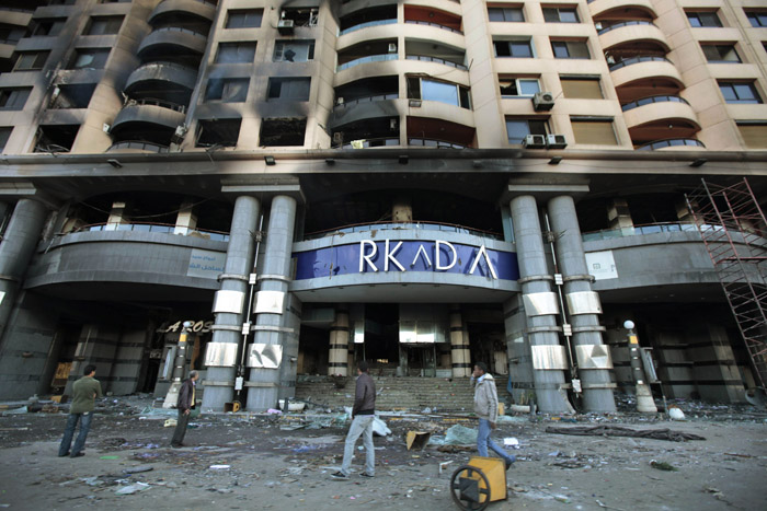 Egyptians walk past Cairo's Arcadia shopping center, which was looted and set on fire recently. The protests engulfing Cairo have shuttered businesses, forced factories to stop operating, closed banks and the stock exchange and limited suppliers' ability to restock store shelves.