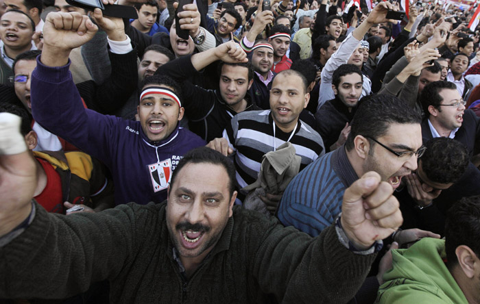 Cheering protesters react as high-ranking Egyptian Army Gen. Hassan El-Rueni, unseen, addresses the continuing anti-government demonstration in Tahrir Square in downtown Cairo today.