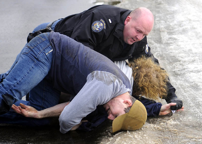 Off-duty state police trooper Jon Leach, left, wrestles Jerry Larravee, center, to the ground with State Police Lt. Brian Scott Monday in Manchester. Leach, who is on sick leave following shoulder surgery, disarmed Larravee, 47, after he pulled a knife after driving in the wrong lane of traffic, according to police.