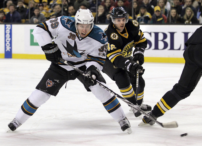 Logan Couture of the Sharks shoots and scores as Boston's David Krejci defends during the first period today in Boston. The Sharks added an empty-net goal in the final seconds for a 2-0 win.
