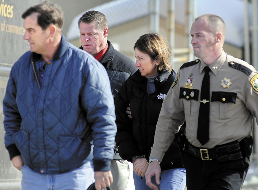 Staff photo by Andy Molloy ARRESTED: Chelsea Selectman Carole Swan, second from right, is led to Kennebec County jail Thursday in handcuffs are being arrested at the sheriff's office in Augusta. Swan was accompanied by, from left, her husband, Marshall Swan; after Kennebec County Sheriff's Department Detective David Bucknam; and Sheriff Randy Liberty.