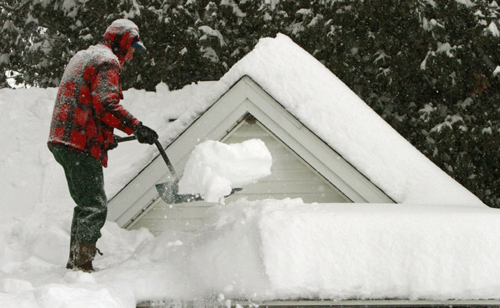 In this Feb. 2 photo, Harry Eastman shovels the snow off his garage roof in Barre, Vt. Doctors across the Northeast are seeing a spike in strained muscles from shoveling snow, broken bones from slick stairs and sidewalks, and dangerously low blood banks as fewer people venture out.