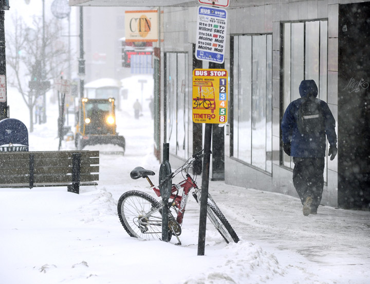 A sidewalk snowplow tries to keep up with the snow accumulating this morning along Congress Street.