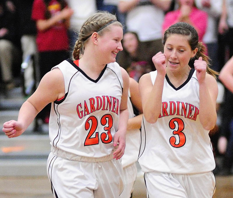 Staff photo by Joe Phelan Gardiner Tigers Liz Kelley, left, and Kelsey Moody celebrate just after the game ended on Tuesday night in the John A. Bragoli Memorial Gym at Gardiner Area High School. Gardiner won the game and advance to the tournament.