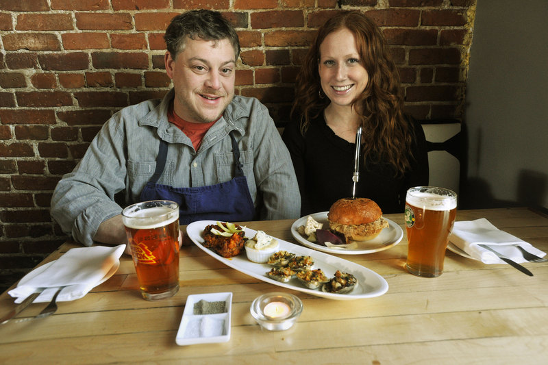 East Ender partners Mitchell Gerow and Megan Schroeter with their buffalo wings, clams casino and pulled pork sandwich.