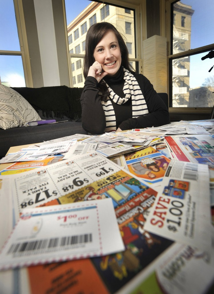 """Chrystie Corns, an """"extreme couponer,"""" displays some of the coupons she's clipped in her Portland office. The author of a blog about coupon collecting, she said she gets the best deals by combining coupons."""