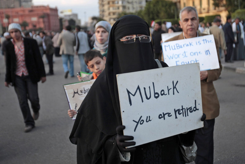 Anti-government protesters carry handwritten signs Monday in Cairo's Tahrir Square. A coalition of opposition groups called for a million people to take to the city's streets today to demand the removal of President Hosni Mubarak.