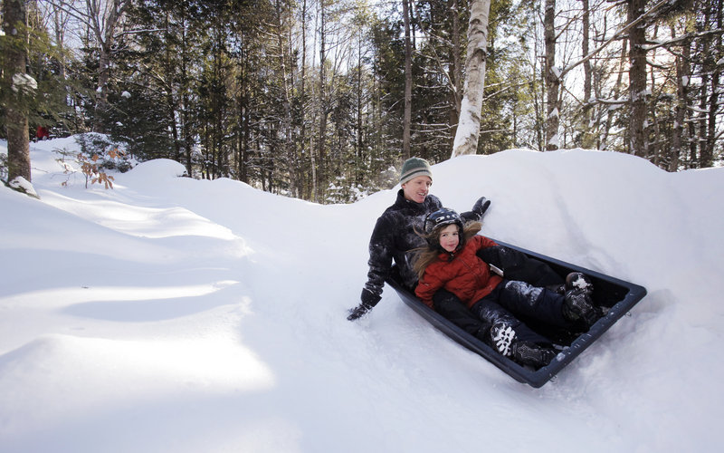 Andy Russ and his daughter Maddy, 7, ride down the family's luge run behind their house in Damariscotta on a recent Saturday. The Russes get in a few runs most mornings before school and work.