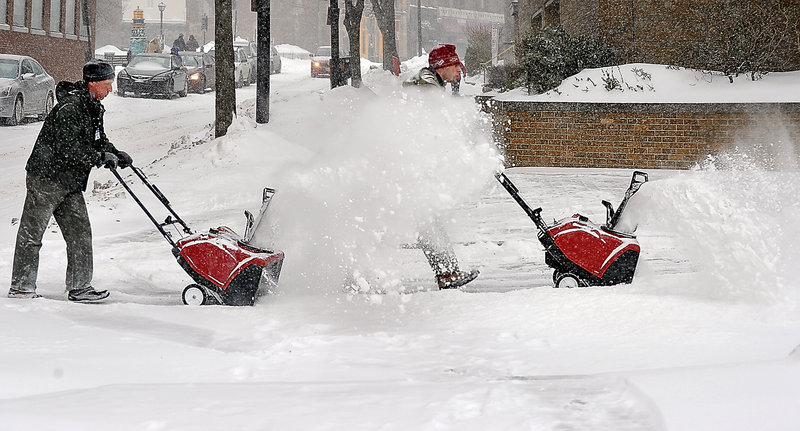 Jay Downs of Commercial Property Services, left, and Tom Moulton of the Dunham Group clear the sidewalks at Two Monument Square.