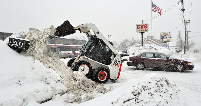 Stuart Collins, property manager for Forest Avenue Plaza, uses a Bobcat tractor to hack away at the growing snowbanks along the plaza's access points Tuesday in advance of the latest blast of wintry weather.