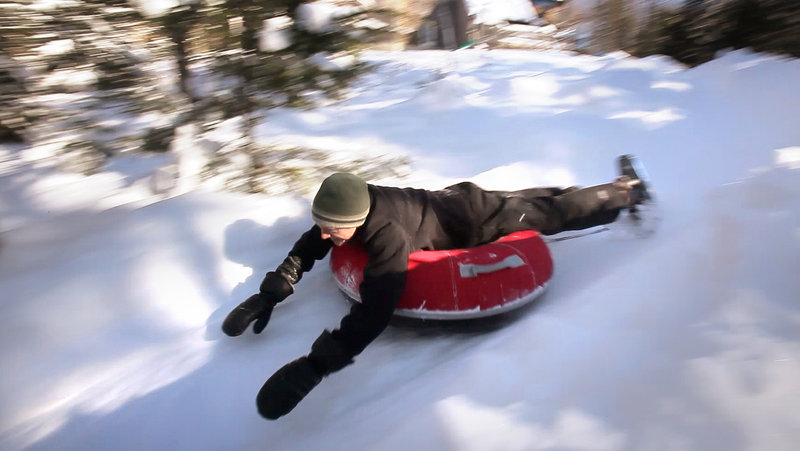 Andy Russ takes a luge run on a tube. The Russes started building their course four years ago, and this winter's abundant snow has given them more frequent use of it.