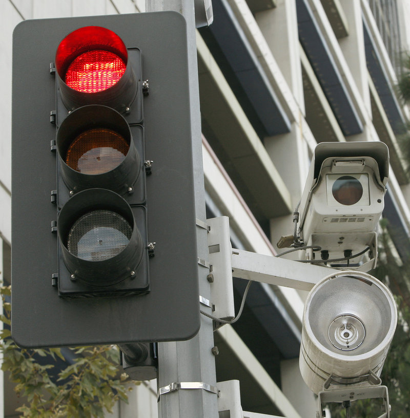 Red light cameras, like this Los Angeles one, have saved 159 lives over five years in 14 cities, a report concludes.