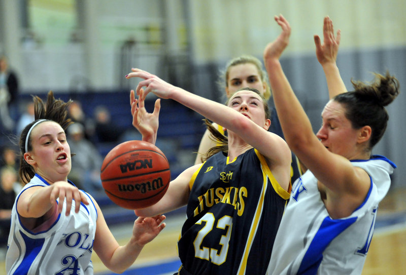 Jules Kowalski, right, of Colby holds her position and draws an offensive foul by Erin McNamara of the University of Southern Maine during a women's basketball game Tuesday night at Waterville. Colby raced to a 37-16 halftime lead and defeated the Huskies, 74-45.