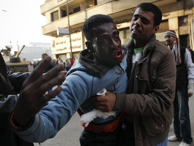 A medic attempts to treat an injured anti-government protester during clashes Wednesday with thousands of Mubarak supporters in Cairo s Tahrir Square.