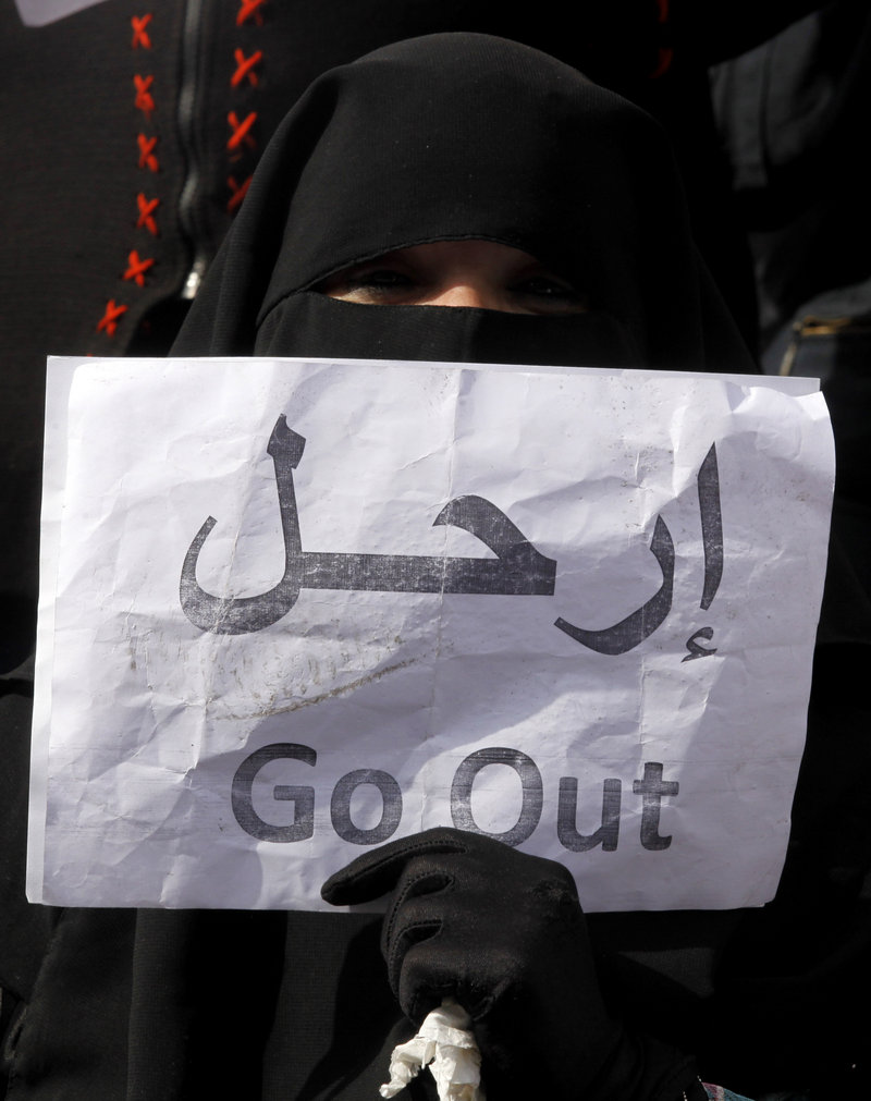 A veiled Egyptian woman holds a poster telling Hosni Mubarak (whose name is in Arabic) to leave.