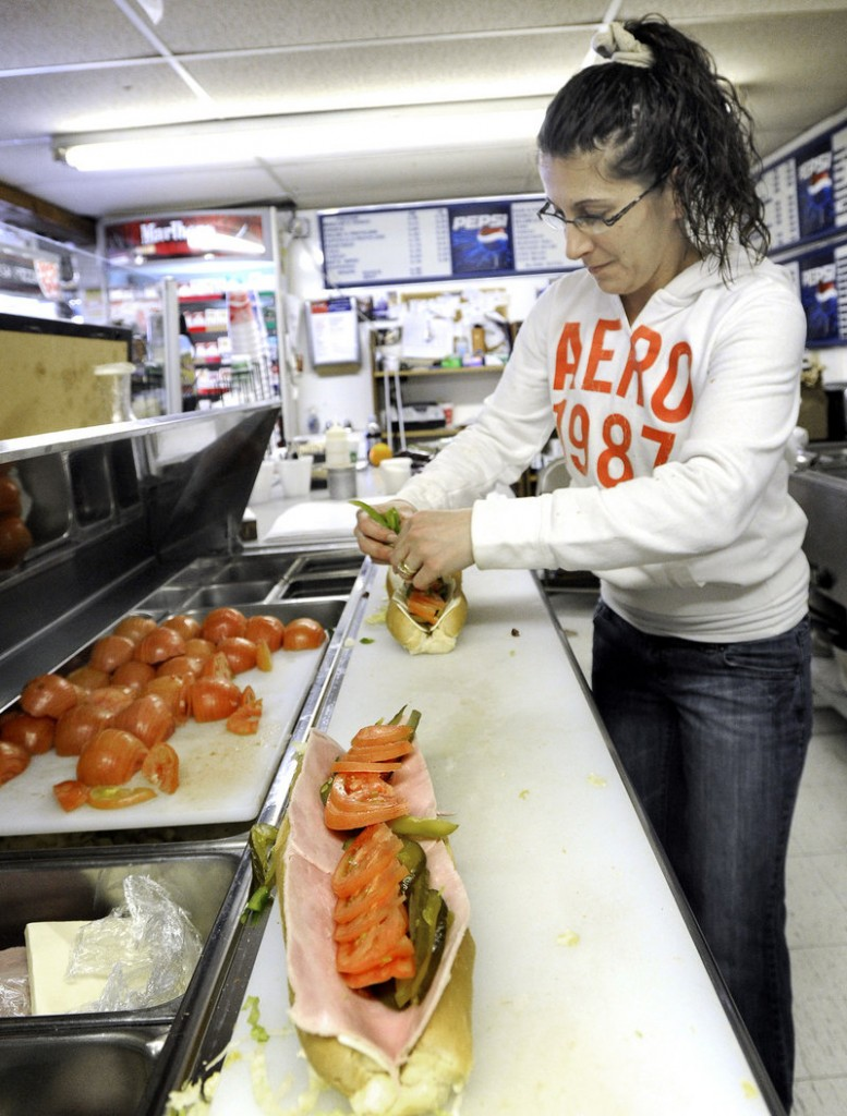 Kerri Grayson makes assorted lunch offerings, including these Italian sandwiches, at Severino's Variety in Westbrook.