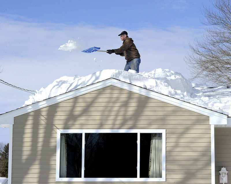 Alan LeVitre shovels snow off his house along Mayflower Street in Westbrook on Friday. Emergency officials are warning Mainers to be aware of the possible dangers that come with snowfall on roofs.