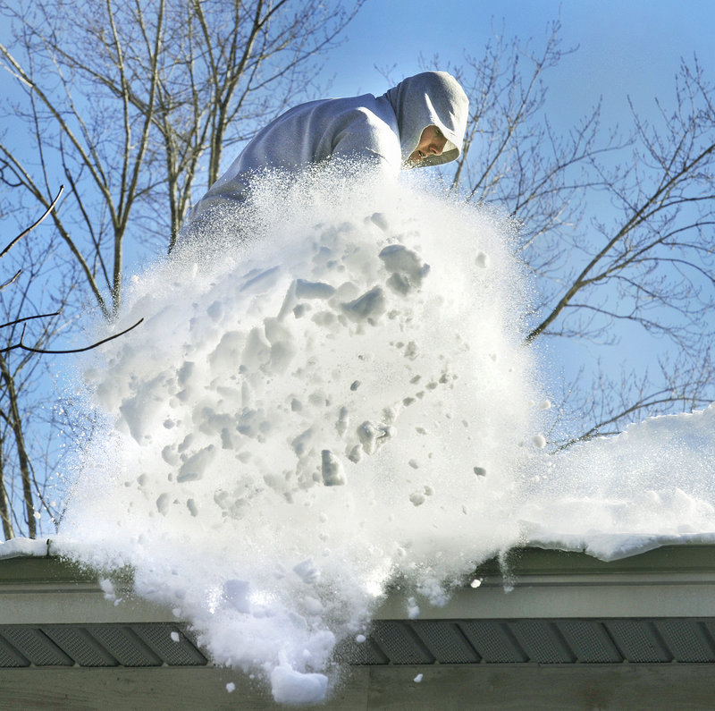 Bill Austin shovels snow from the roof of a home in North Yarmouth on Friday. While property owners may be able to safely remove snow themselves, officials say they should also consider hiring a professional.