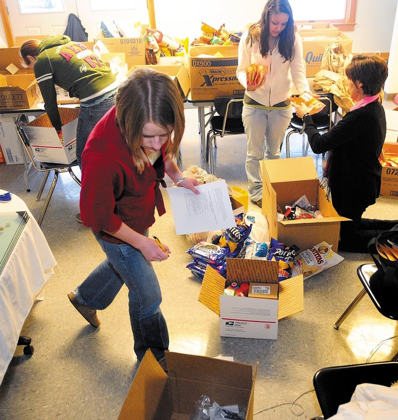 Erskine Academy students Alivia Spicer, foreground, Erica LeSieg, top left, and Brandi Moulton and staffer Diane Dow pack items for an Army brigade commanded by an Erskine graduate.