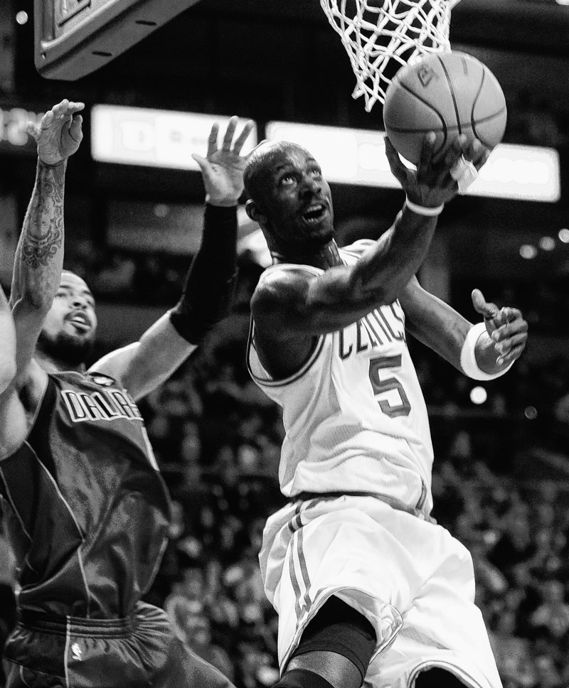 With Dallas' Tyson Chandler trailing, Boston's Kevin Garnett drives to the basket during the first quarter Friday night at the TD Garden in Boston.