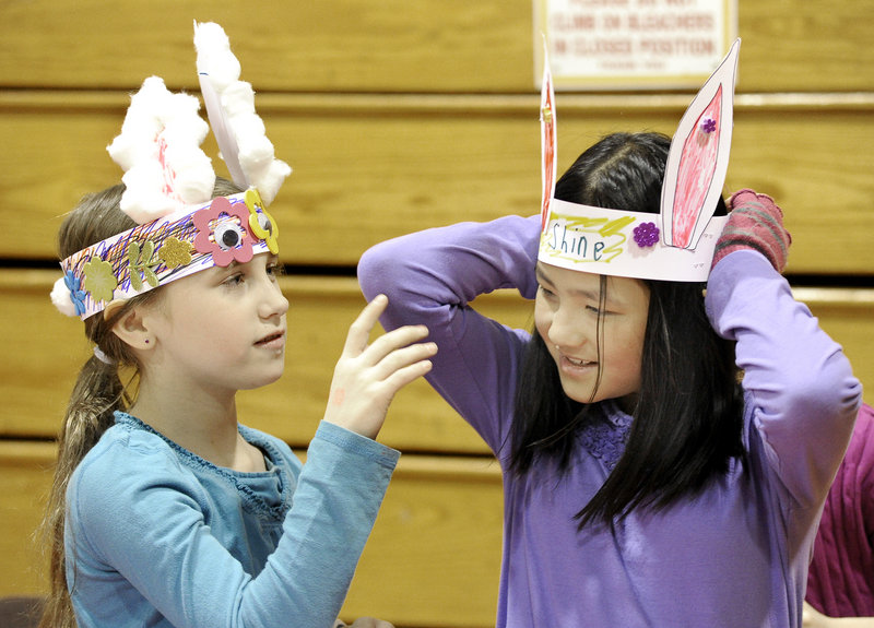 Nine-year-olds Abigale O'Brion of Hollis and Grace Soares of Westbrook try on rabbit headdresses they'd made during a Chinese New Year event at McAuley High School.