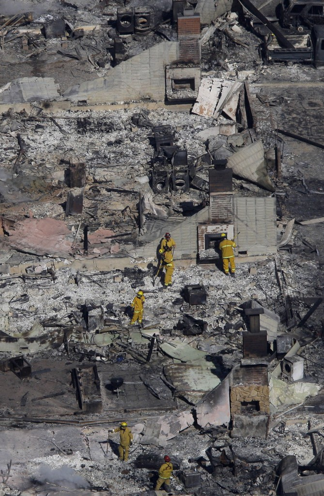 Fire crews examine the remains of homes damaged by a massive fire last September in a mostly residential neighborhood in San Bruno, Calif. An Associated Press investigation found that the utility, Pacific Gas & Electric Co., agreed years ago that remotely operated valves did a better job of protecting public safety than manual ones. But it opted against using them widely across its network.