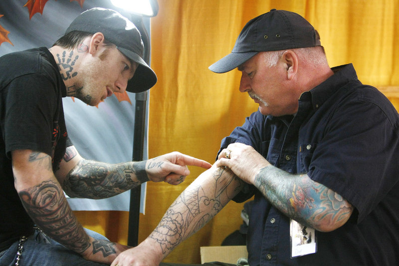 "Dave Buchanan, right, of Portland and artist James McGrory of Fianna Studio in Portland discuss a design on Buchanan's arm during an annual tattoo show in South Portland on Sunday. ""If someone says it doesn't hurt, they're lying,"" said Buchanan, a tollbooth worker who serves as a daily advertisement for McGrory when he reaches out to take money."