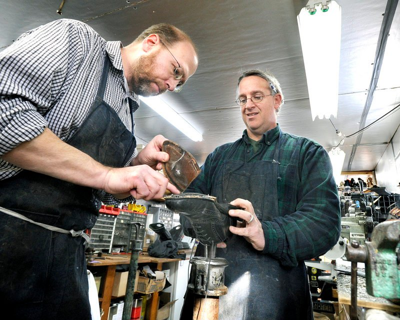 Ray Routhier, left, works on replacing the sole of a shoe with Paul Rowland at Paul's Shoe Repair in Westbrook.