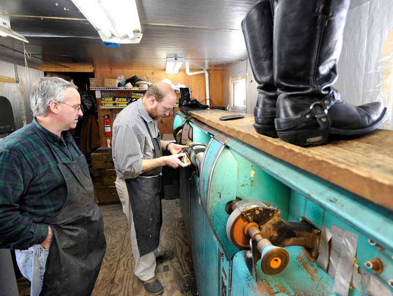 Ray Routhier, right, works on one of the machines with Paul Rowland at Paul's Shoe Repair in Westbrook.