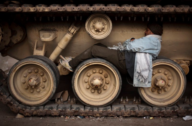 An Egyptian anti-Mubarak protester sleeps on the wheels of a tank at Tahrir Square in Cairo, Egypt, on Sunday.