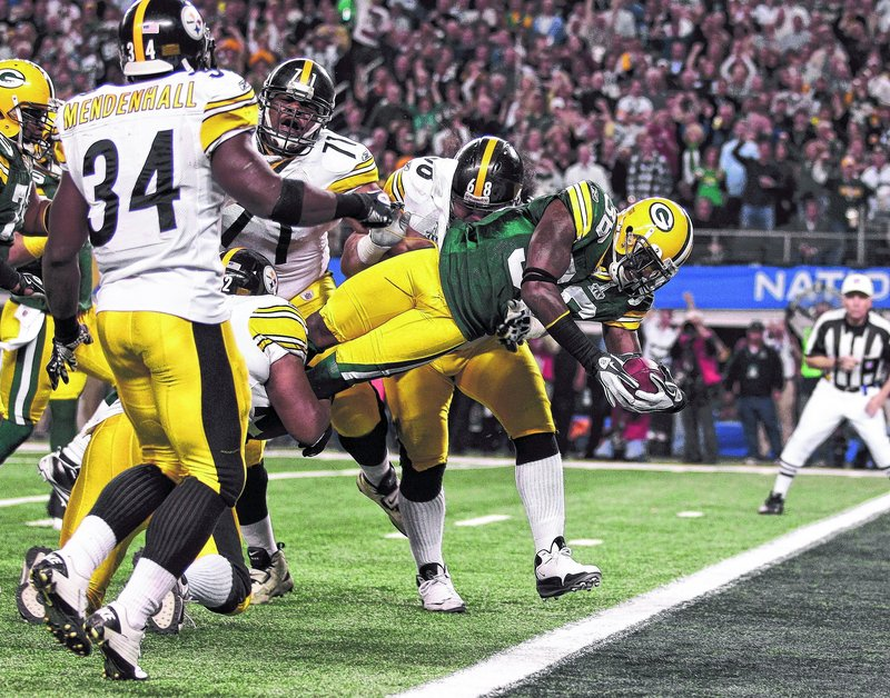 Green Bay's Nick Collins dives past Pittsburgh's Chris Kemoeatu (68), Flozell Adams (71) and Rashard Mendenhall (34) for a touchdown after intercepting a pass by Pittsburgh's Ben Roethlisberger during the first half Sunday. Green Bay forced two interceptions and a fumble.