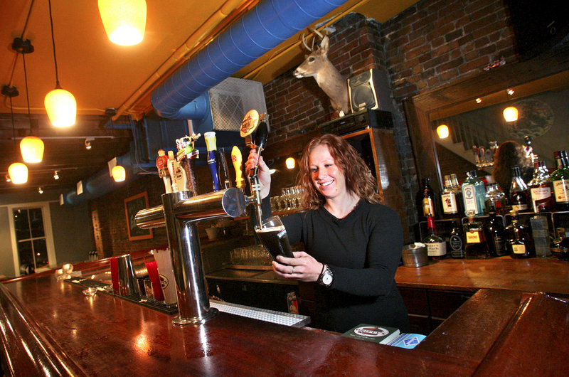 Meg Schroeter, one of the owners of the East Ender, draws a beer at one of the two bars. The East Ender also carries 30 to 40 different bottled beers.