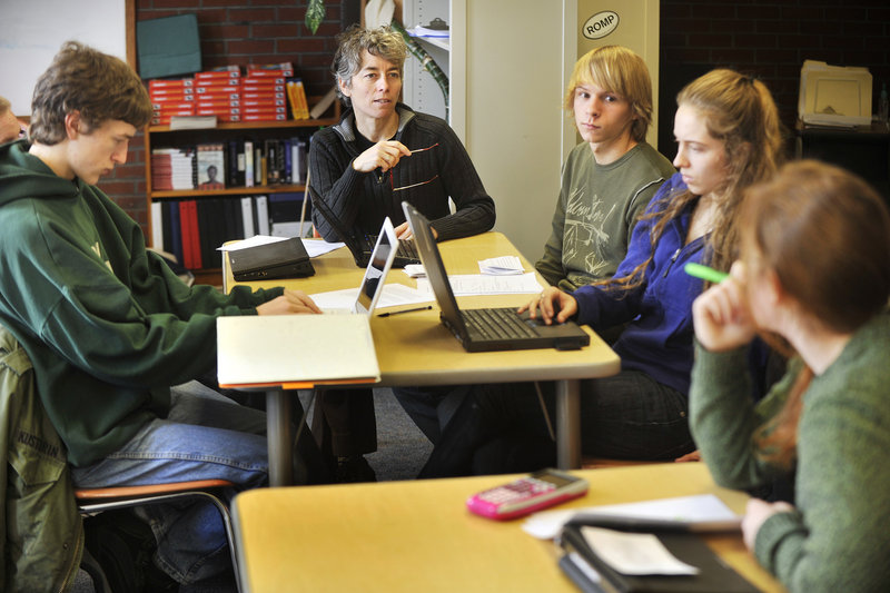 Teacher Susan McCray works with humanities students Monday at Casco Bay High School in Portland. Started in 2005, the school emphasizes real-world learning experiences.
