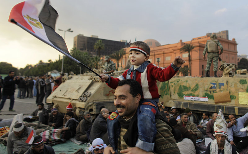 A boy sitting on the shoulders of an anti-government protester waves the Egyptian flag in front of armored personnel carriers Monday at the continuing demonstration in Tahrir Square in downtown Cairo.