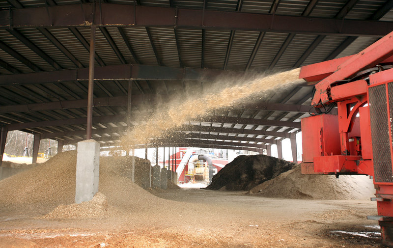 A wood chipper shoots chips into a pile for drying at the plant that produces Maine's Choice premium wood pellets.
