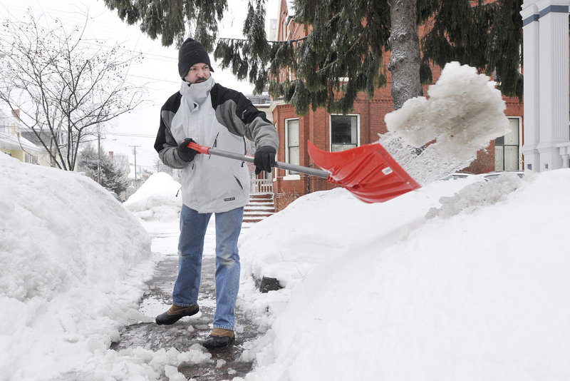 Chad Vinkemulder clears a wintry mix of snow, slush and ice Tuesday from the sidewalk in front of his home on West Street in Portland. Shoveling today will be a little harder to tolerate, with gusty winds making it feel extra cold.