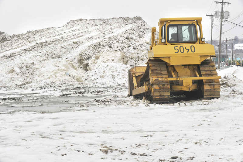 A bulldozer awaits more snow Tuesday afternoon at Portland's snow dump on Somerset Street in the city's Bayside neighborhood.