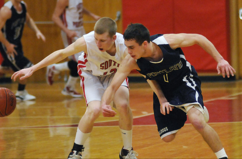 Tanner Hyland of South Portland, left, and Nick Volger of Portland fight for a loose ball Tuesday night. Peter Donato led Portland with 18 points.